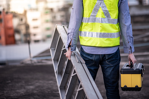 Maintenance worker man with safety helmet and green vest carrying aluminium step ladder and tool box at construction site. Civil engineering, Architecture builder and building service concepts