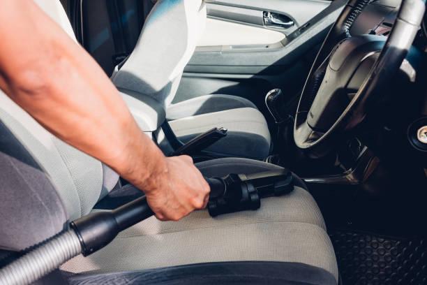 worker man cleaning dust interior vacuum inside car - close up auto foto e immagini stock