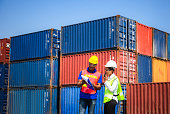 istock Worker man in hardhat and safety vest holding clipboard checklist and Female foreman talks on two-way radio control loading containers box from cargo 1214447827