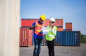 istock Worker man in hardhat and safety vest holding clipboard checklist and Female foreman talks on two-way radio control loading containers box from cargo 1214447837
