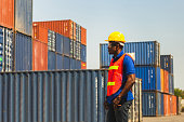 istock Worker man in hardhat and safety vest standing at containers cargo, Foreman control loading containers box from cargo 1211363612