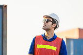 istock Worker man in hardhat and safety vest standing at containers cargo, Engineer man checking containers box from cargo 1222735972