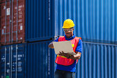 istock Worker man in hardhat with clipping path and safety vest holding laptop, Foreman control loading containers box from cargo 1212446980
