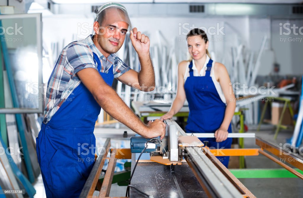 Worker man is ready to work on circular saw in assembly shop - Royalty-free Adult Stock Photo