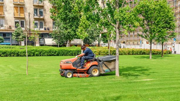 arbeiter fahren rasenmäher mini-traktor auf einem stadtparkplatz gras, gartengeräte konzept - gartenbau betrieb stock-fotos und bilder