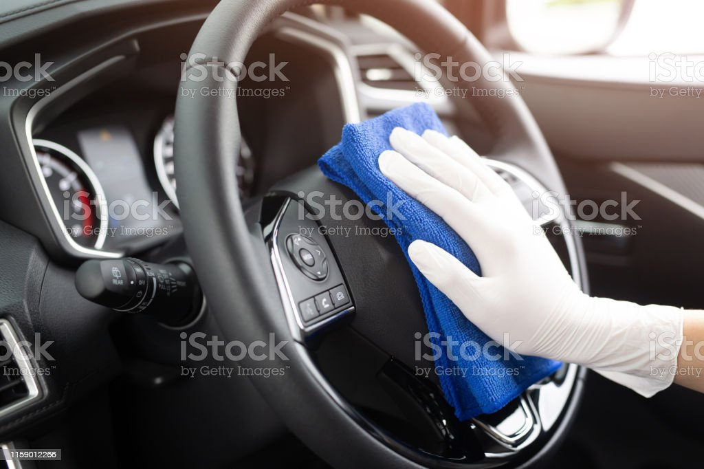 工人男子戴手套清洗汽車內部主控台用超細纖維布,細節,洗車服務的概念。複製空間。 - 免版稅一個人圖庫照片