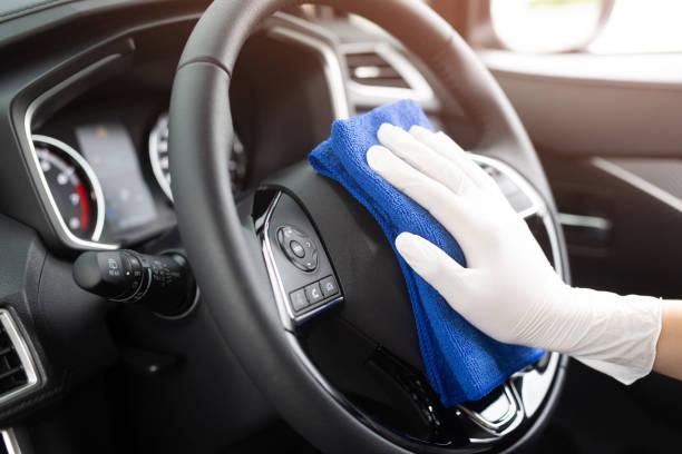 trabajador hombre usar guantes de limpieza de la consola interior del coche con paño de microfibra, detalles, concepto de servicio de lavado de coches. espacio de copia. - primer plano fotografías e imágenes de stock