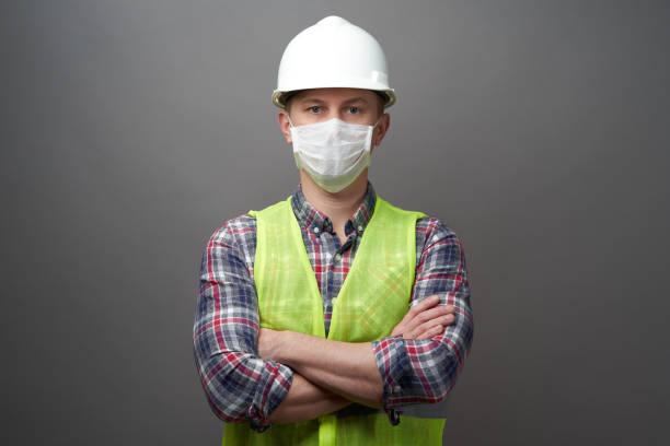 工人男子戴著衛生口罩和防護帽圖像檔