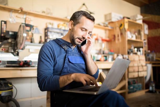 worker managing manufactory - owner laptop smartphone foto e immagini stock