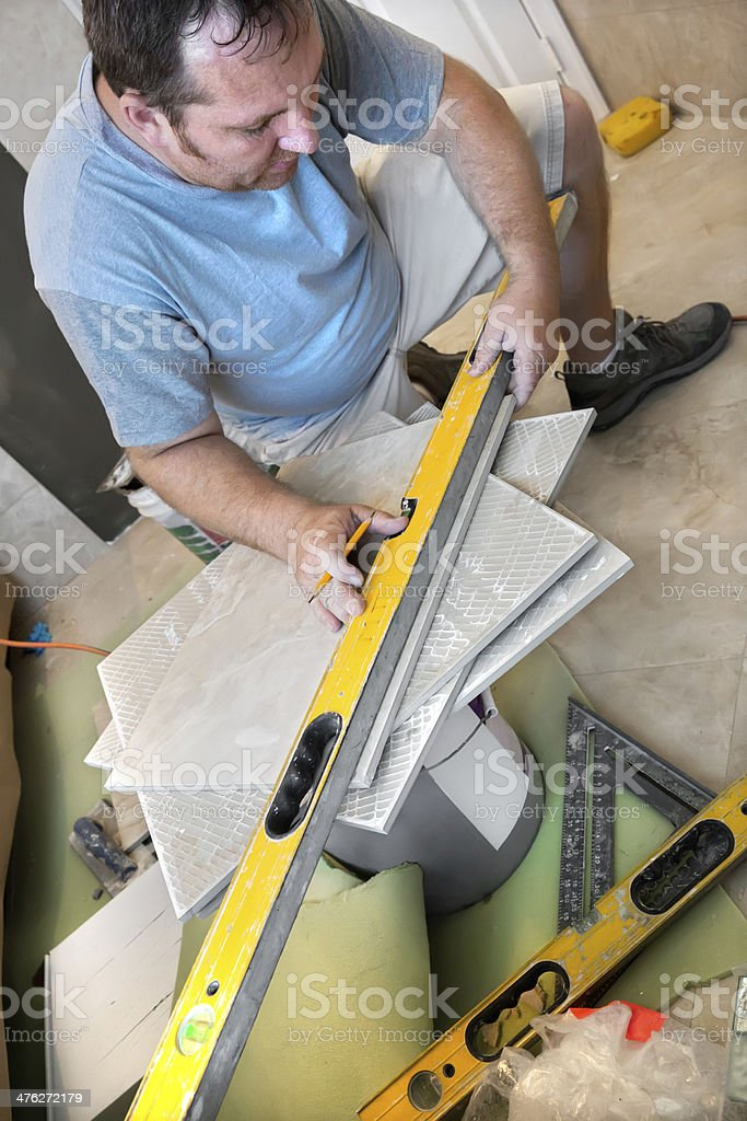 Worker measuring before cutting a wall tile royalty-free stock photo