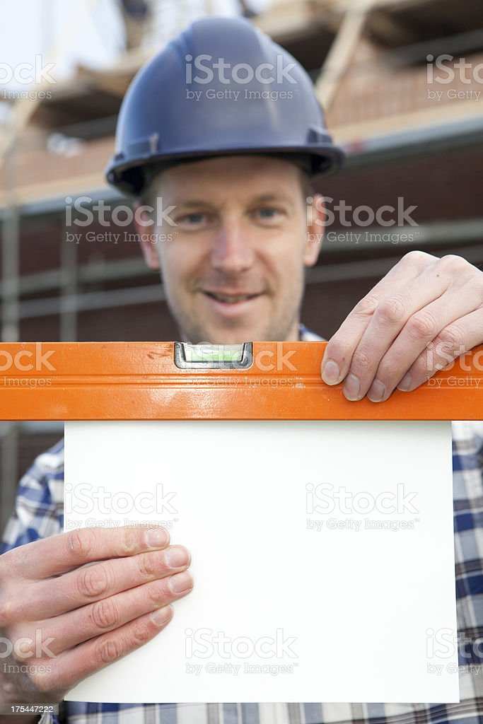 Worker Measuring Blank Paper With Spirit Level royalty-free stock photo