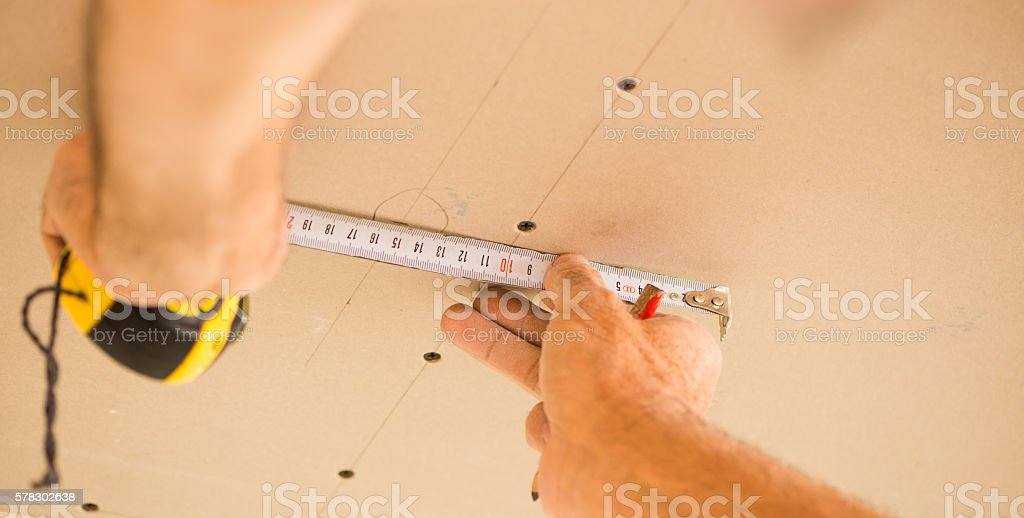 worker metering distance on ceiling stock photo