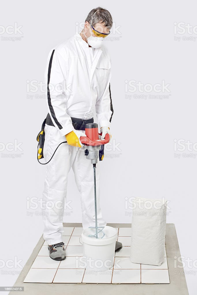 Worker mix tile adhesive with machine tool royalty-free stock photo