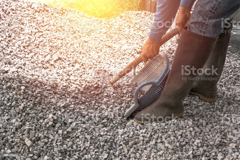 Worker mixing concrete cement mortar at construction site. stock photo