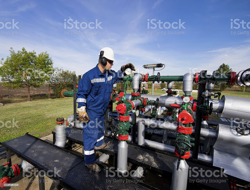 A worker monitoring a meter attached to a system of pipes stock photo