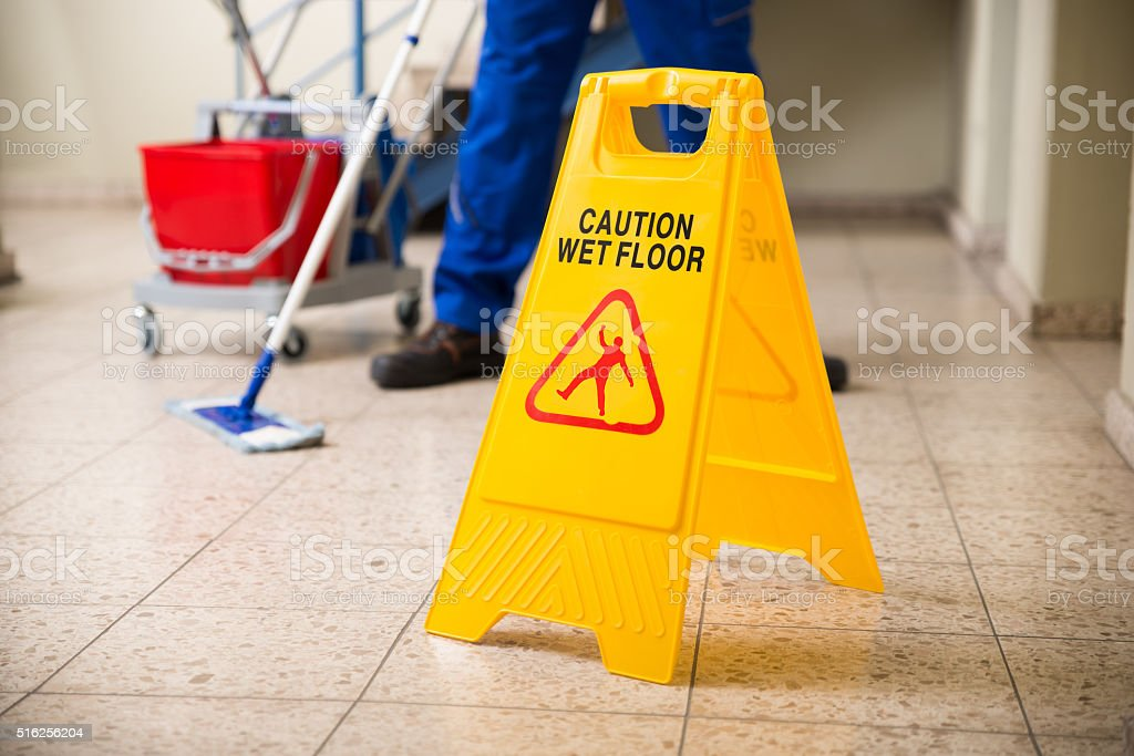 Worker Mopping Floor With Wet Floor Caution Sign stock photo