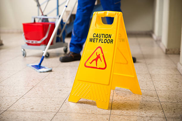 worker mopping floor with wet floor caution sign - custodian stock pictures, royalty-free photos & images