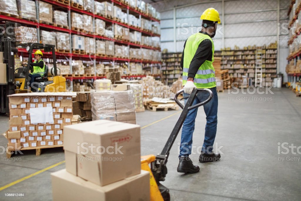 Worker moving boxes in hand truck in warehouse stock photo