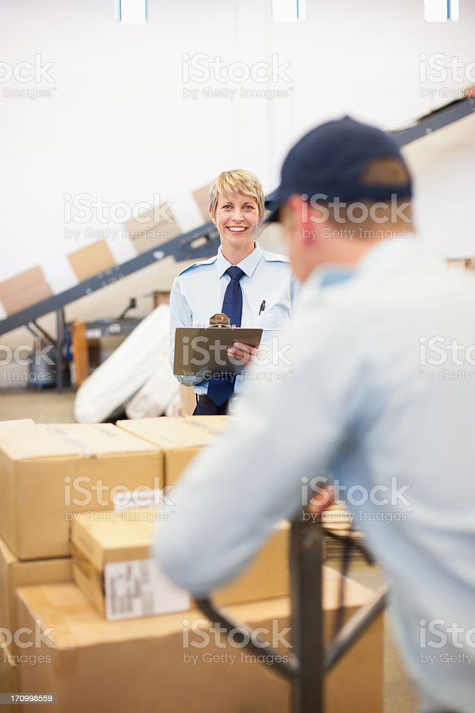 Worker moving boxes on hand cart in shipping area royalty-free stock photo