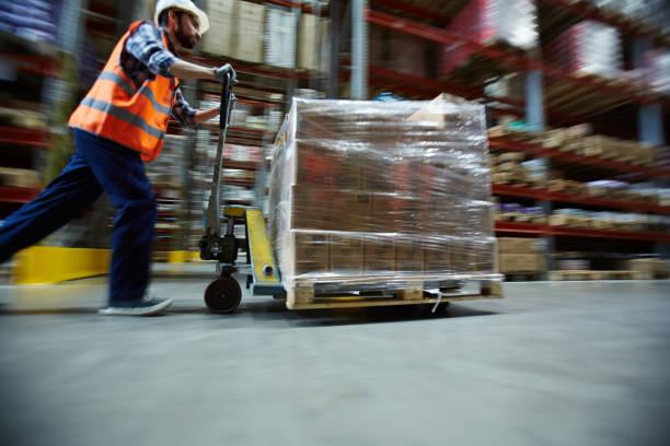 Travailleur se déplaçant au détail de marchandises en entrepôt grand - Photo