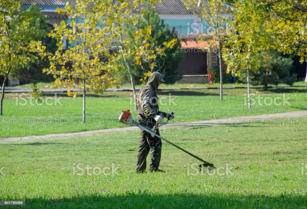 Worker Mowing Grass With A Gasoline Brush Trimmer Stock Photo More