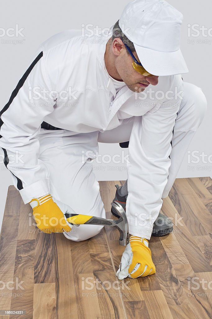 Worker nailed a nail with hammer on the wooden floor royalty-free stock photo