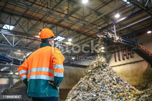 Low angle rear view of young male worker in helmet, pollution mask, and reflective clothing observing waste falling from conveyor belt onto pile at facility.