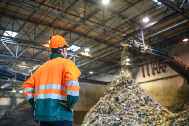 Worker Observing Processing of Waste at Recycling Facility stock photo