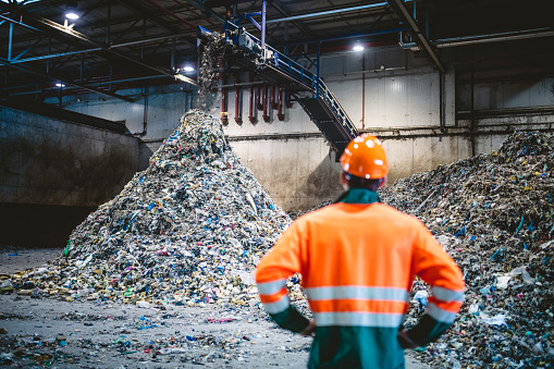 Rear view of young male worker in helmet, pollution mask, and reflective clothing observing waste falling from conveyor belt onto pile at facility.
