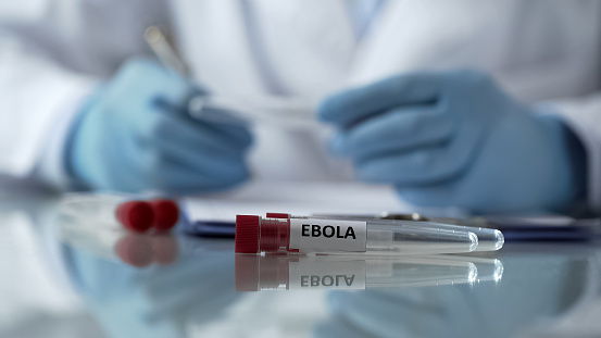 Worker Of Center For Disease Control Describing Effects Of Ebola Virus Mutation Stock Photo - Download Image Now