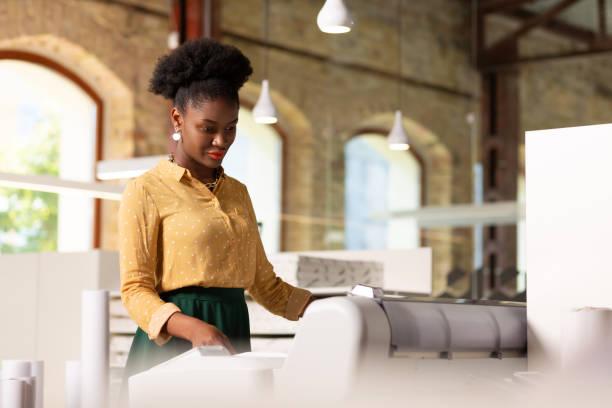 Mitarbeiter der Verlagsagentur, die während der Arbeit einen Drucker verwendet – Foto