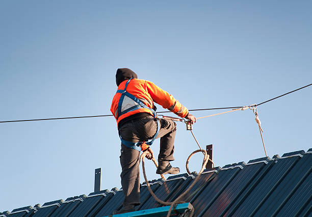 Worker on a roof Construction Worker wearing safety harness attached to a safety line on a pitched roof safety harness stock pictures, royalty-free photos & images