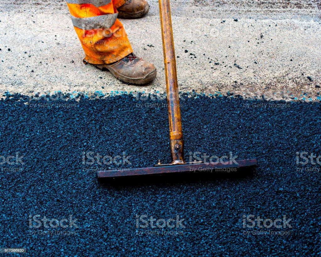 Worker on Asphalting paver machine during Road street repairing works stock photo