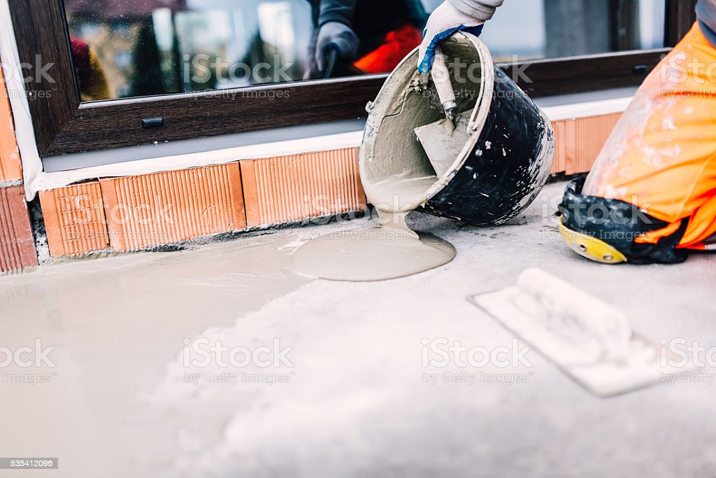 worker on construction site pouring sealant from bucket for waterproofing stock photo