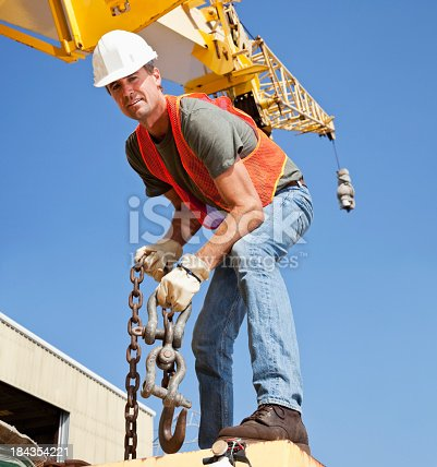 Low angle view of a construction worker standing, bending over, on a crane preparing steel chains.and hook.  He is wearing an orange safety vest, white hard hat, jeans, work boots and protective gloves, smiling at the camera. Above him in the background we see the long part of the crane against the clear blue sky.