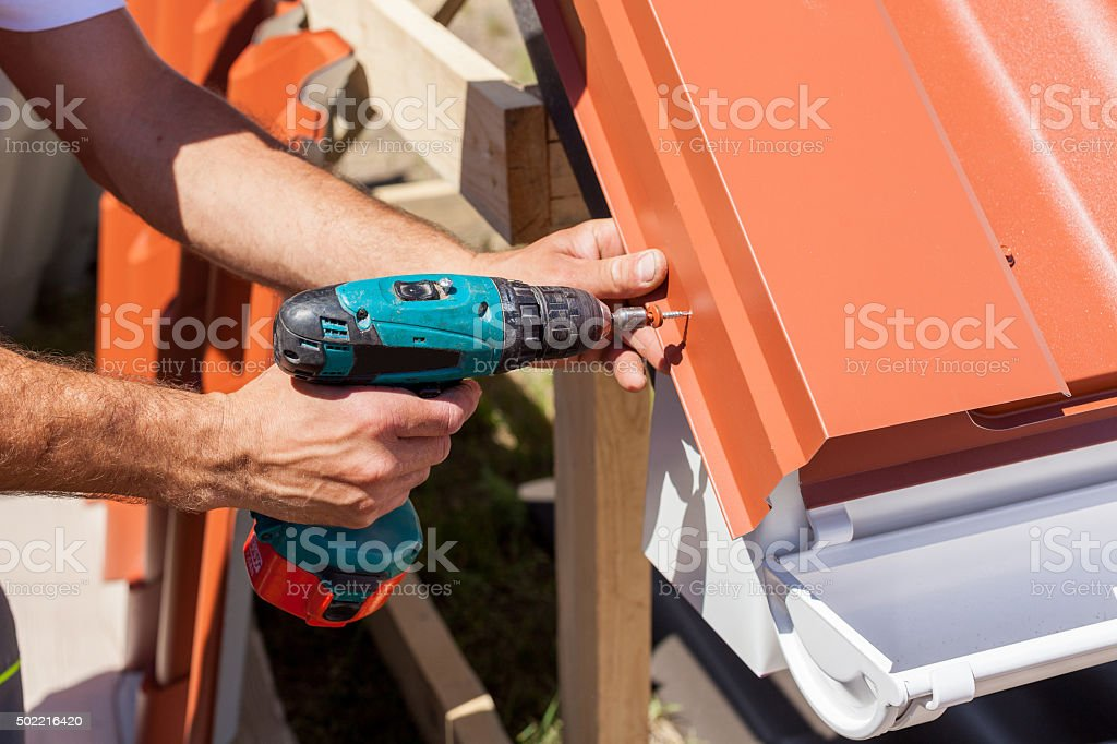 Worker on roof with electric drill installing red metal tile stock photo