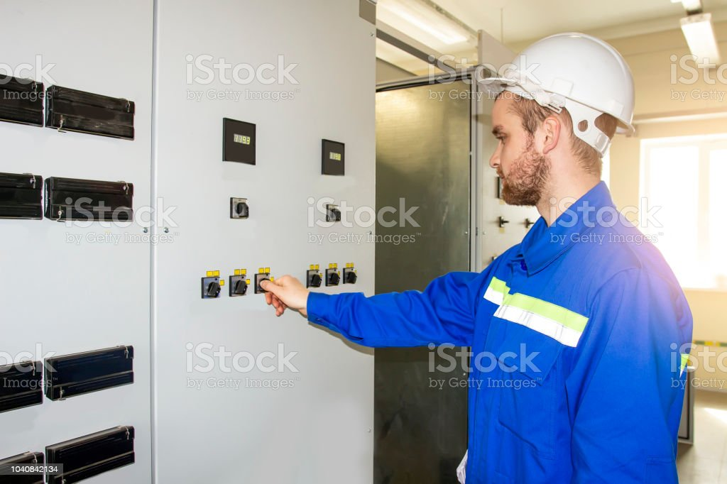 Worker on the control panel of industrial equipment. Automation of...
