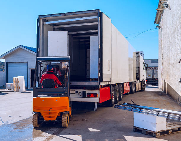 worker on the loader loads long white semi-trailer - lorries unloading stock photos and pictures