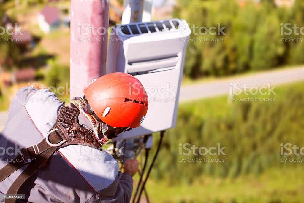 worker on the telecommunications tower with a wrench stock photo