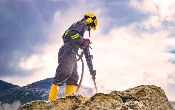 Worker on top of a rock Worker with helmet and protective suit using a drilling machine on top of a large rock drill stock pictures, royalty-free photos & images