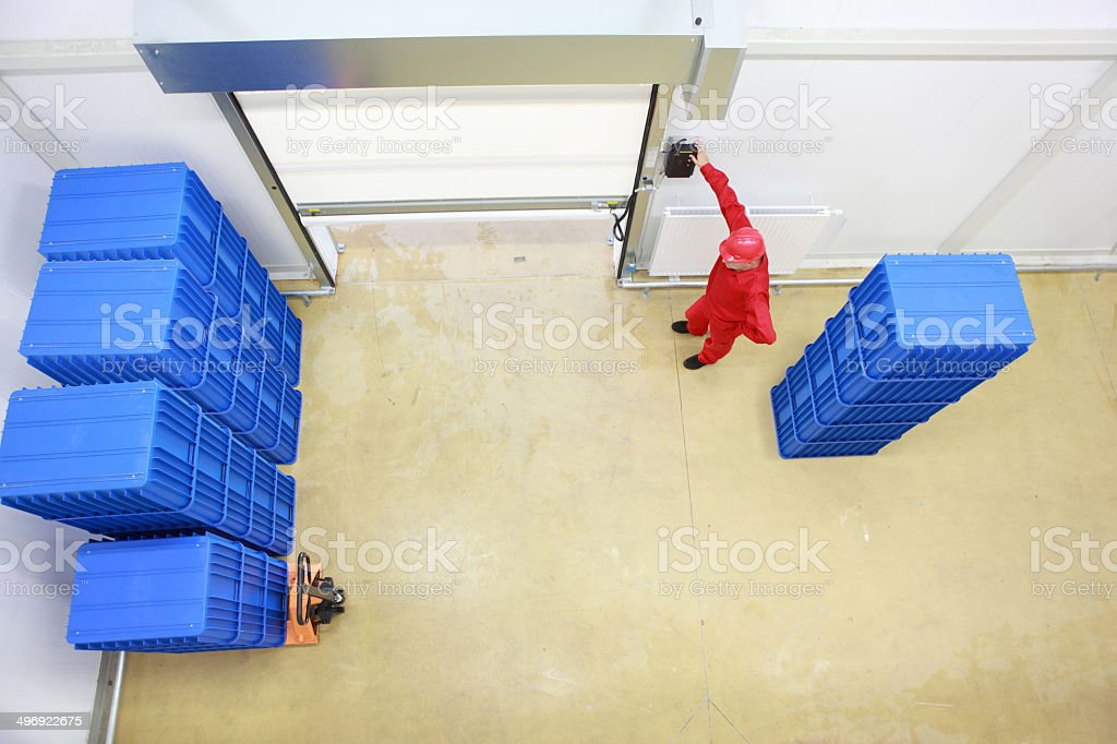 worker  opening a gate  in small warehouse with plastic boxes stock photo