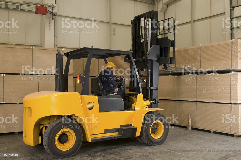 Worker operates yellow forklift in warehouse stock photo
