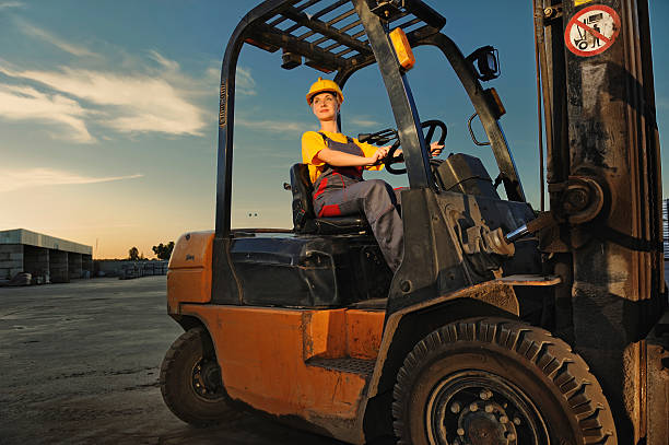 A worker operating a forklift at dusk stock photo