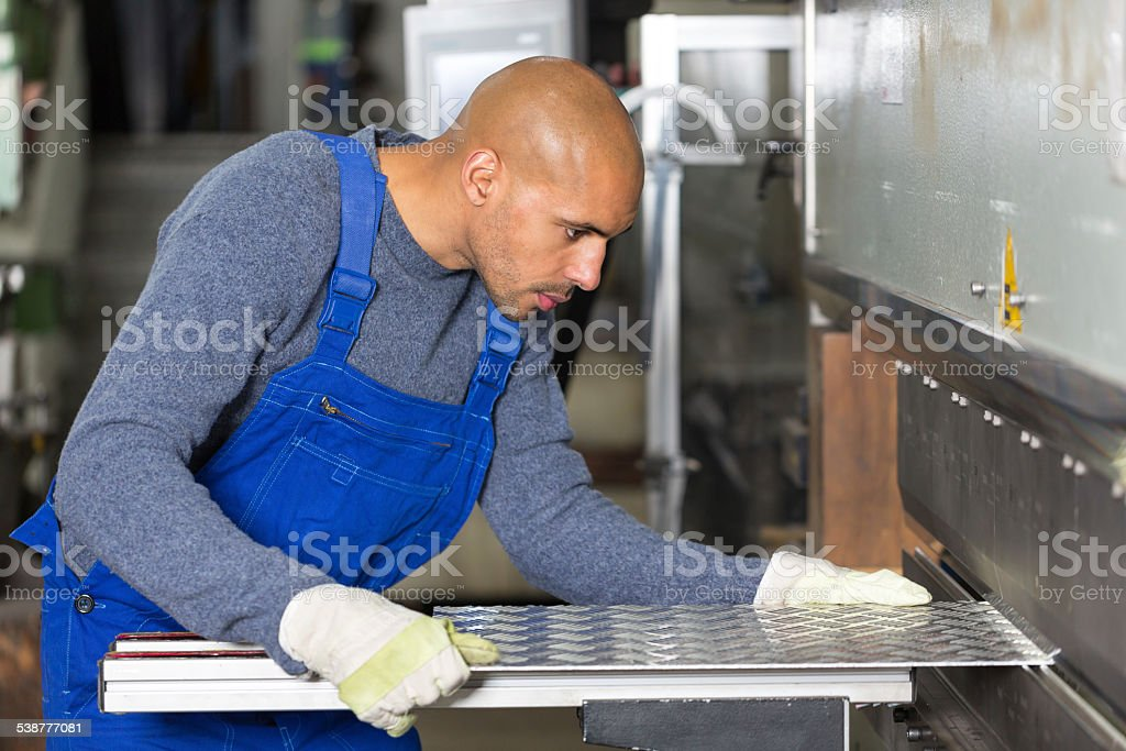 Worker operating a machine for bending sheet metal stock photo