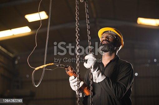 1047558948 istock photo Worker operating chain hoist at factory 1264282293
