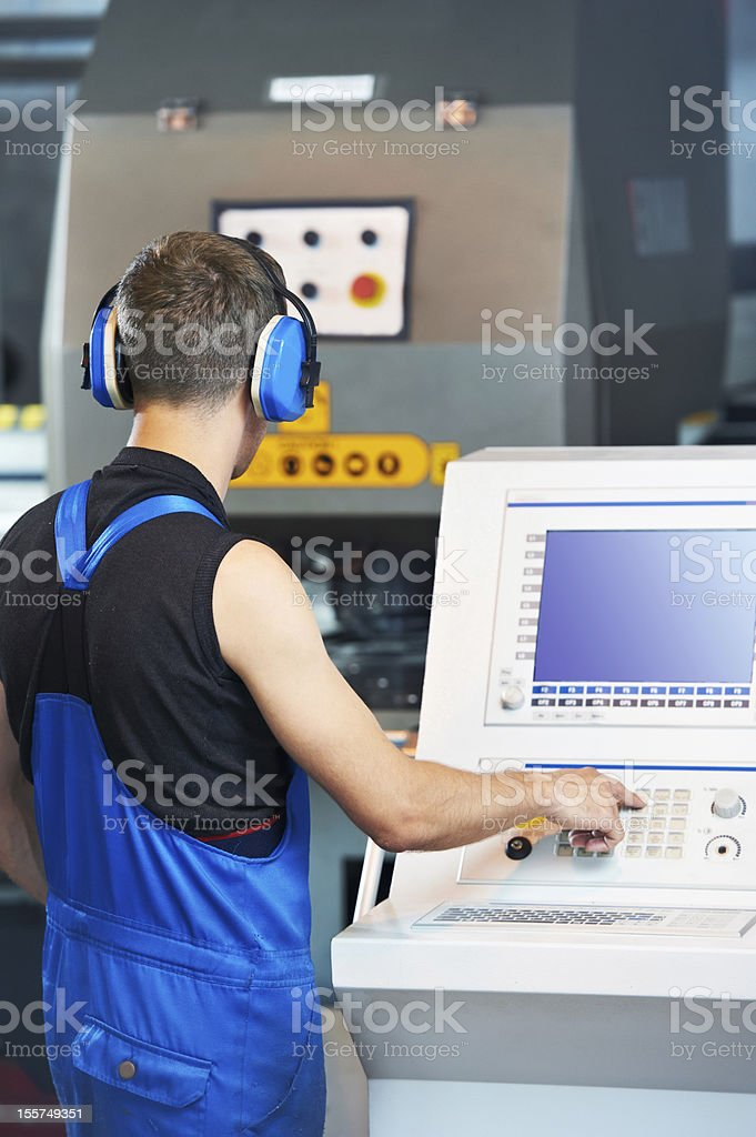 worker operating cnc punch press stock photo