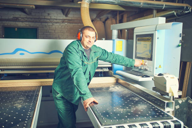 Worker operating computer controlled machinery in factory stock photo