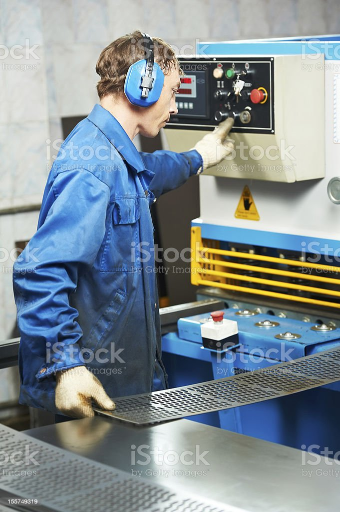 worker operating guillotine shears machine stock photo