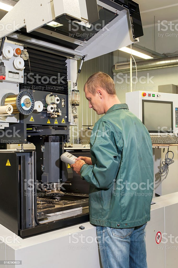 Worker operating industrial cnc machine in workshop. stock photo