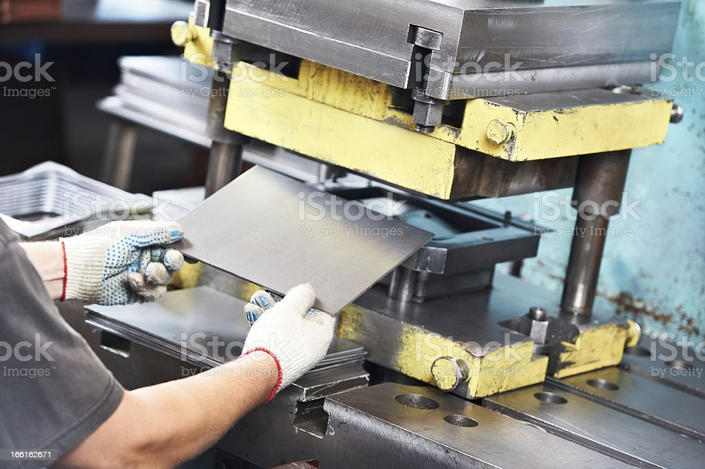 worker operating metal sheet press machine stock photo